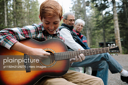 Grandparents watching grandson playing guitar at campsite - p1192m2129275 by Hero Images