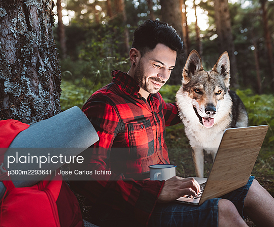 Mid adult man working through laptop while sitting with dog in forest - p300m2293641 by Jose Carlos Ichiro