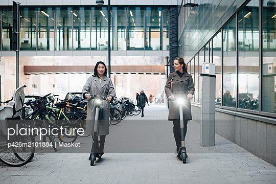 Full length of confident female colleagues riding electric push scooter on footpath by building in city - p426m2101884 by Maskot