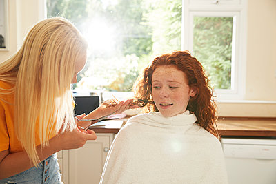 Teenage girl cutting hair for worried friend in sunny kitchen - p1023m2238501 by Himalayan Pics