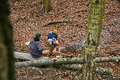 Two men in the forest by campfire - p1573m2175260 by Christian Bendel