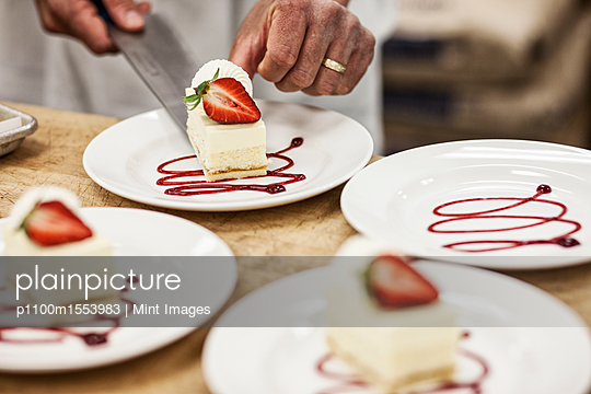 Chef hands placing a layered desert on a plate, presentation of a sweet dish.  - p1100m1553983 by Mint Images