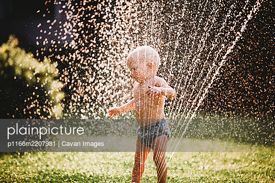 White baby standing in garden playing with water from the sprinkler - p1166m2207981 by Cavan Images