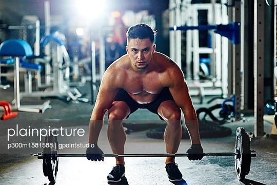 Man lifting barbell in gym - p300m1581588 von gpointstudio