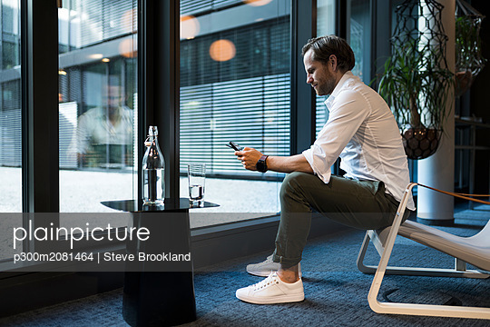 Casual businessman working in lounge area of a coworking space, using digital tablet - p300m2081464 by Steve Brookland