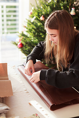 Girl packing Christmas gift - p312m1558475 by Christina Strehlow