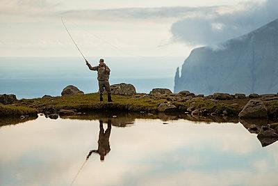 Man fishing in lake - p312m2051451 by Hans Berggren