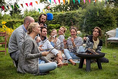 Freunde im Schrebergarten rösten Marshmallows - p788m1165259 von Lisa Krechting