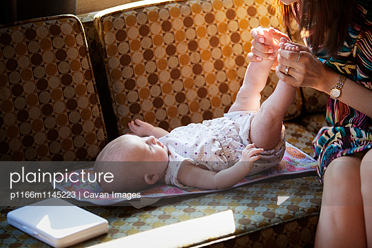 Cropped image of woman holding baby girl's feet on sofa - p1166m1145223 by Cavan Images