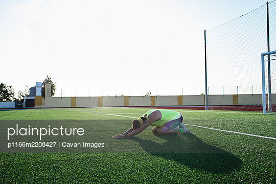 young man practices stretching on the grass after his daily training - p1166m2208427 by Cavan Images