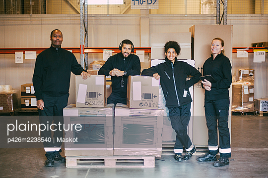 Portrait of smiling manual workers standing with box containers at logistics warehouse - p426m2238540 by Maskot