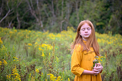 Young Girl in Yellow Dress in a Field of Flowers - p1166m2212555 by Cavan Images