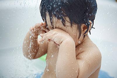 Baby girl rubbing eyes while taking bath at home - p300m2287492 by Arman Zhenikeyev