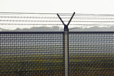 View of security fence at airport - p300m660066f by Tom Hoenig