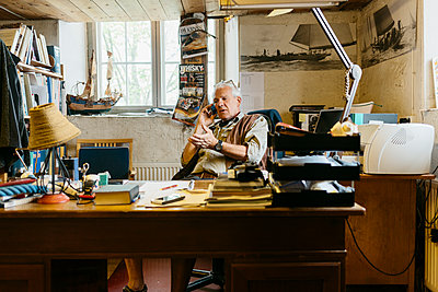 Rope maker talking on his cell phone at his desk in shop - p352m2041244 by Folio Images