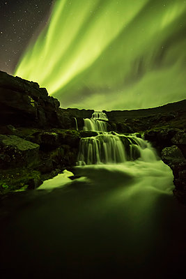 Northern Lights, or Aurora Borealis, glowing over waterfalls and a stream; Iceland - p442m1141512 by Robert Postma
