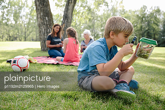 Young boy looking at bugs in jar with magnifying glass - p1192m2129965 by Hero Images