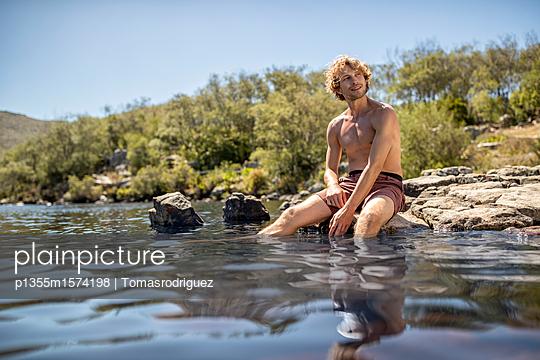 Junger Mann badet seine Füße im Fluss - p1355m1574198 von Tomasrodriguez