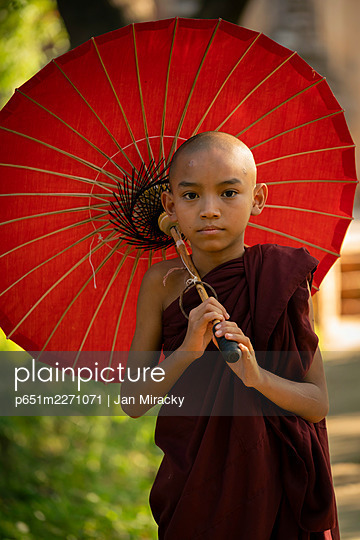 Portrait of novice monk with red umbrella, Bagan, Mandalay Region, Myanmar - p651m2271071 by Jan Miracky
