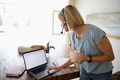 Woman with headset working from home, using laptop at dining table - p1192m2088351 by Hero Images