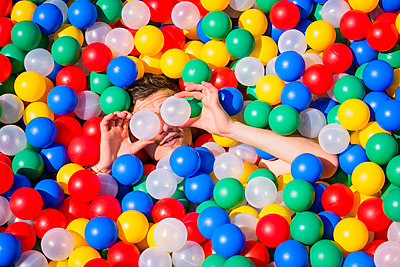 Playful young man laying in multicolor ball pool - p301m2075613 by Sven Hagolani