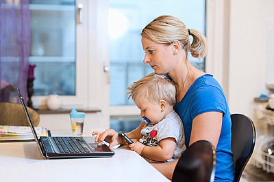Mother working on laptop while baby boy using smart phone on her lap at home - p426m1017822f by Maskot