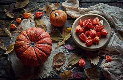 Pumpkins and autumn leaves on wooden table - p555m1301644 by Valeriya Tikhonova