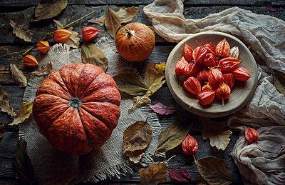 Pumpkins and autumn leaves on wooden table - p555m1301644 by Valeriya Tikhonova