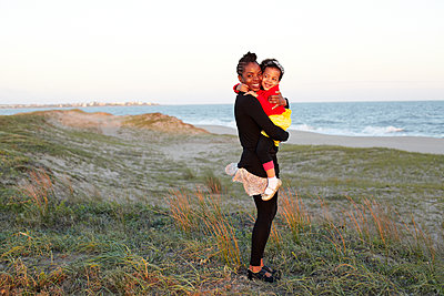 Mother hugging daughter on beach - p555m1454081 by Granger Wootz