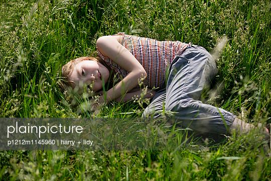 Mädchen liegt auf der Seite im Gras - p1212m1145960 von harry + lidy