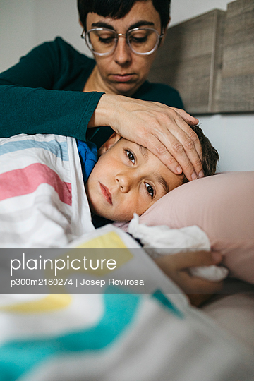 Portrait of sick boy lying in bed while his mother touching his forehead - p300m2180274 by Josep Rovirosa