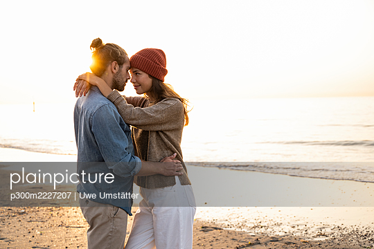 Romantic young couple standing face to face while looking at each other during sunset - p300m2227207 by Uwe Umstätter