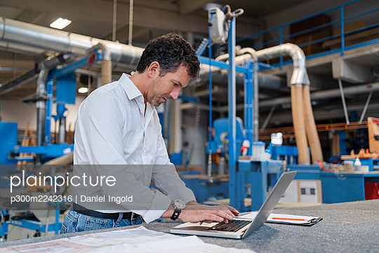 Portrait of carpenter using laptop in production hall - p300m2242316 by Daniel Ingold