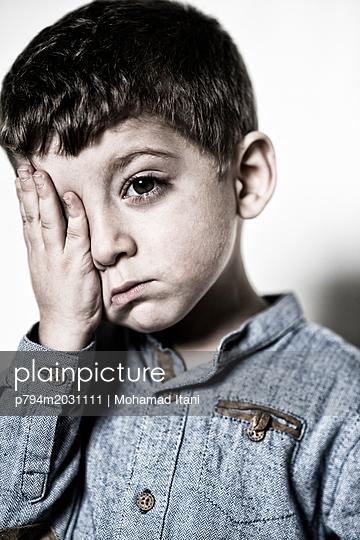 Trauriger kleiner Junge, Hand bedeckt sein Auge - p794m2031111 von Mohamad Itani