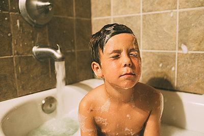 Shirtless boy with eyes closed bathing in bathtub - p1166m1554246 by Cavan Images