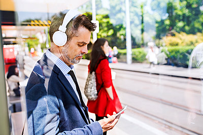 Businessman with smartphone and headphones waiting at the bus stop - p300m1469679 by HalfPoint