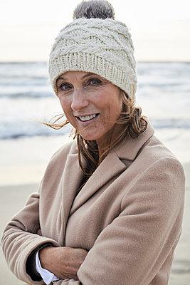 Spain, Menorca, portrait of smiling senior woman wearing bobble hat on the beach in winter - p300m2080430 by Ivan Gener