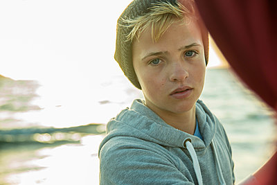 Portrait of teenage boy standing on the beach - p300m965433f by Uwe Umstätter