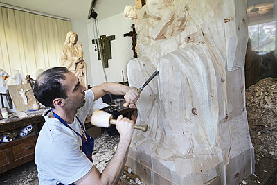 Sculptor chiseling figure from wood - p429m747166f by Stefano Gilera
