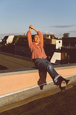 Frau genießt die Zeitr auf dem Hausdach - p432m2203194 von mia takahara