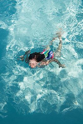 Mädchen schwimmt im Pool - p954m1585914 von Heidi Mayer