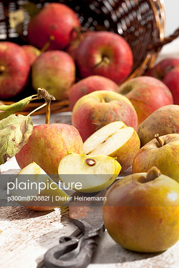 Organic apples (Malus), basket and a knife on white wooden table, studio shot - p300m873882f by Dieter Heinemann