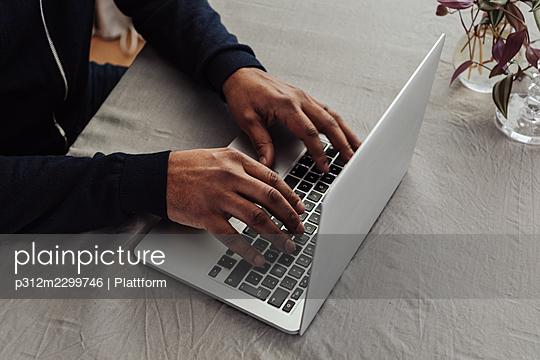 Man's hands on laptop keyboard - p312m2299746 by Plattform
