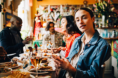 Portrait of confident young woman sitting with smart phone against friends at table in restaurant during dinner party - p426m2046325 by Maskot