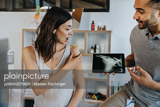 Physiotherapist discussing x-ray image of shoulder with patient in practice, Cologne, NRW, Germany - p300m2276825 von Mareen Fischinger