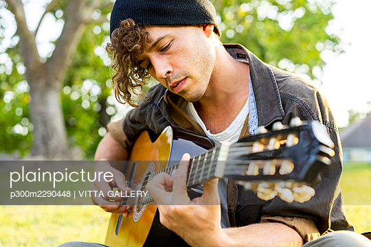 Handsome young man playing guitar at park - p300m2290448 by VITTA GALLERY
