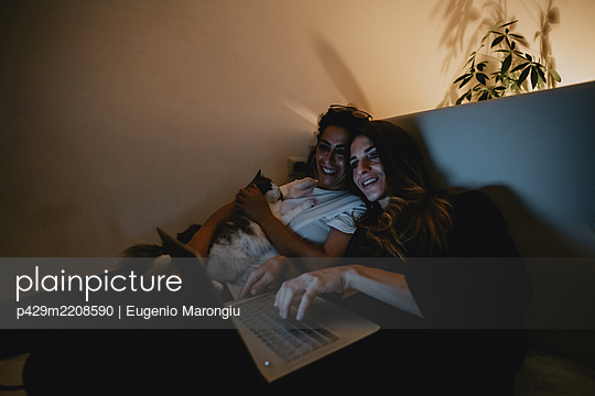 Two smiling women with brown hair sitting on sofa with cat, looking at laptop. - p429m2208590 by Eugenio Marongiu