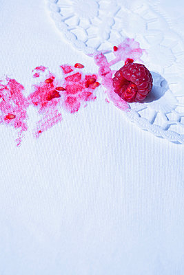 White tablecloth with stains of a smeared raspberry - p1149m2093469 by Yvonne Röder