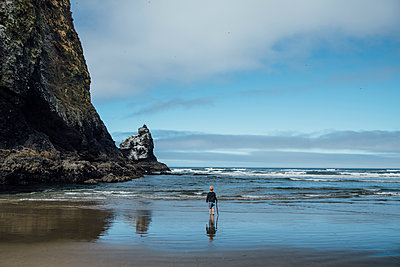 Full length rear view of boy walking on shore at beach against sky - p1166m1524547 by Cavan Images