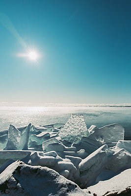 Large flat pieces of ice piled up along the shore of a lake in winter. - p1166m2169198 by Cavan Images
